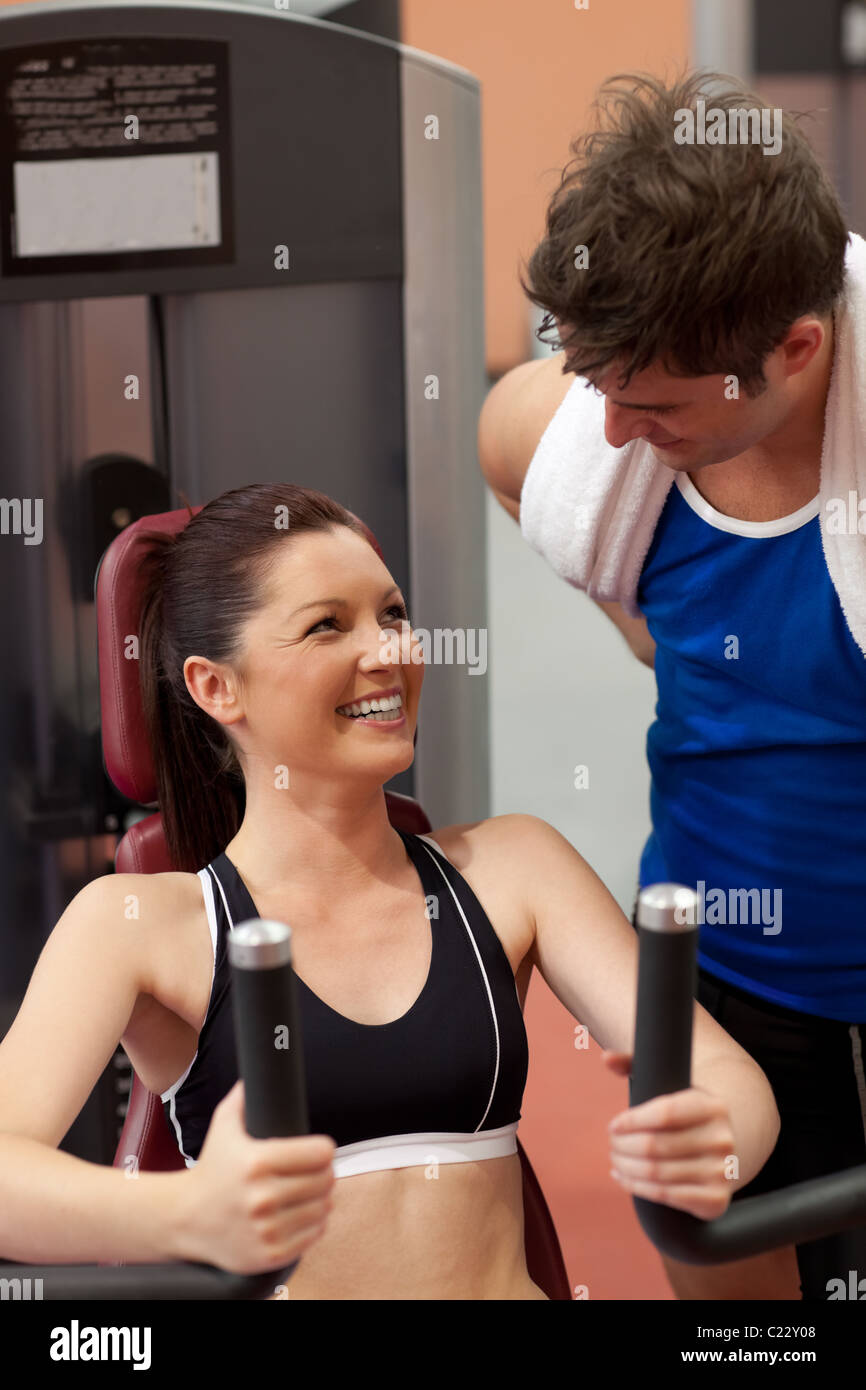Joyful athletic woman using a shoulder press with her coach - Stock Image