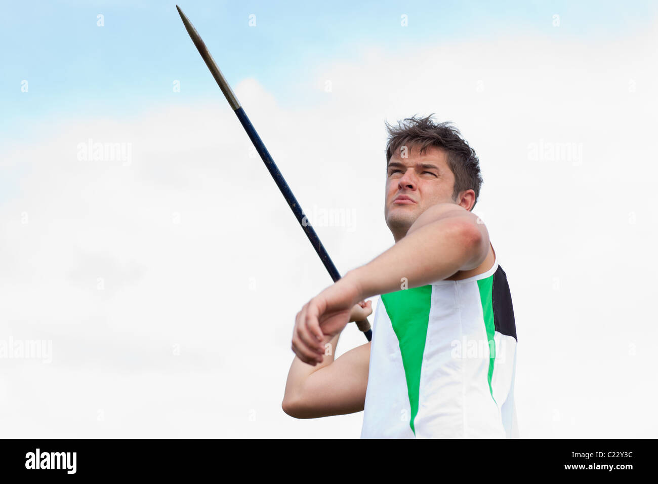 Determined sportsman throwing the javelin - Stock Image