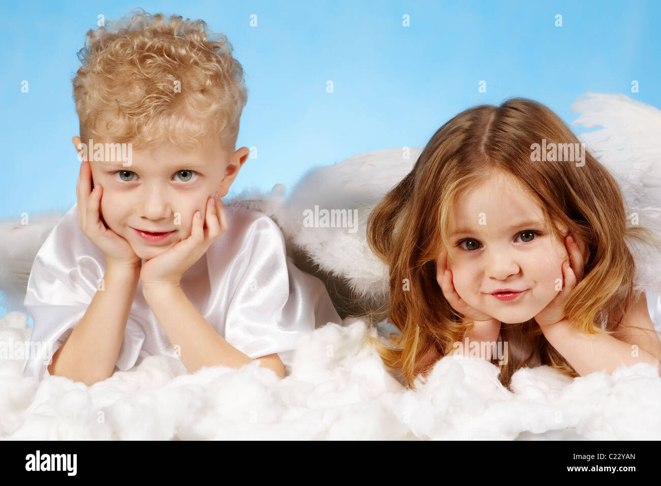 Small boy and girl in angelic costume lying on white cloud - Stock Image