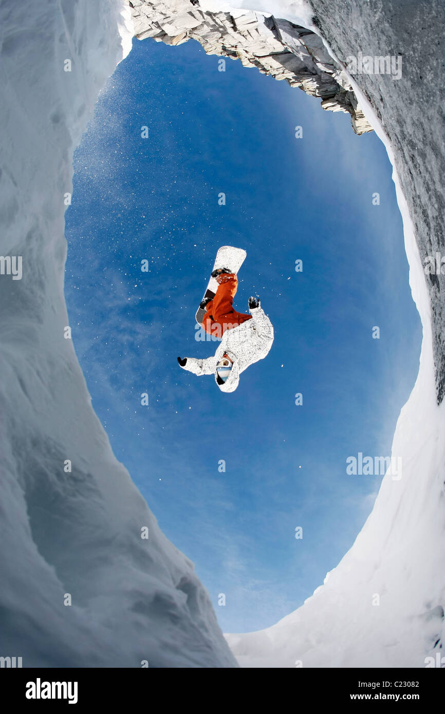 View from below of snowboarder jumping over rocky mountainside in winter - Stock Image