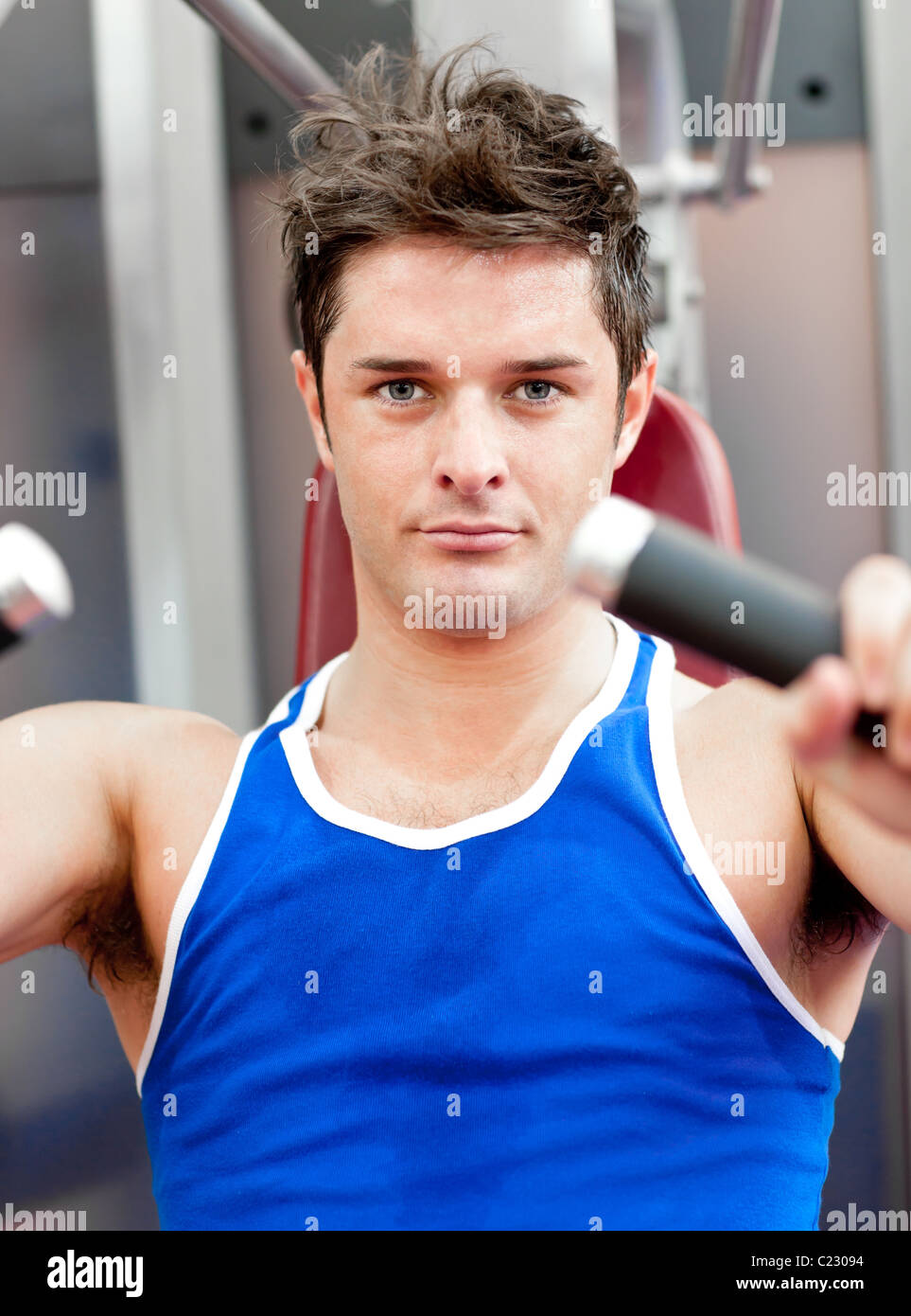 Charming athletic man using a bench press - Stock Image