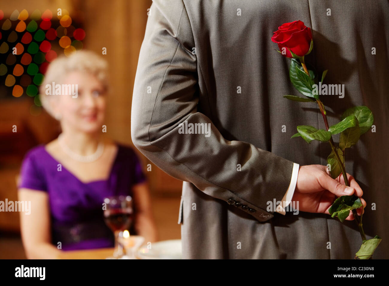 Rear view of man holding red rose in hand on background of intrigued female - Stock Image