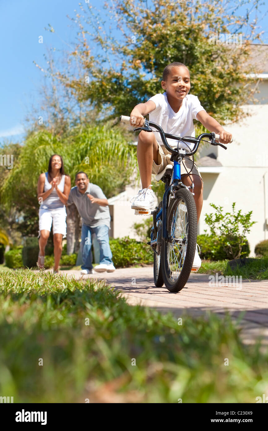 A young African American family with boy child riding his bicycle and his happy excited parents giving encouragement - Stock Image