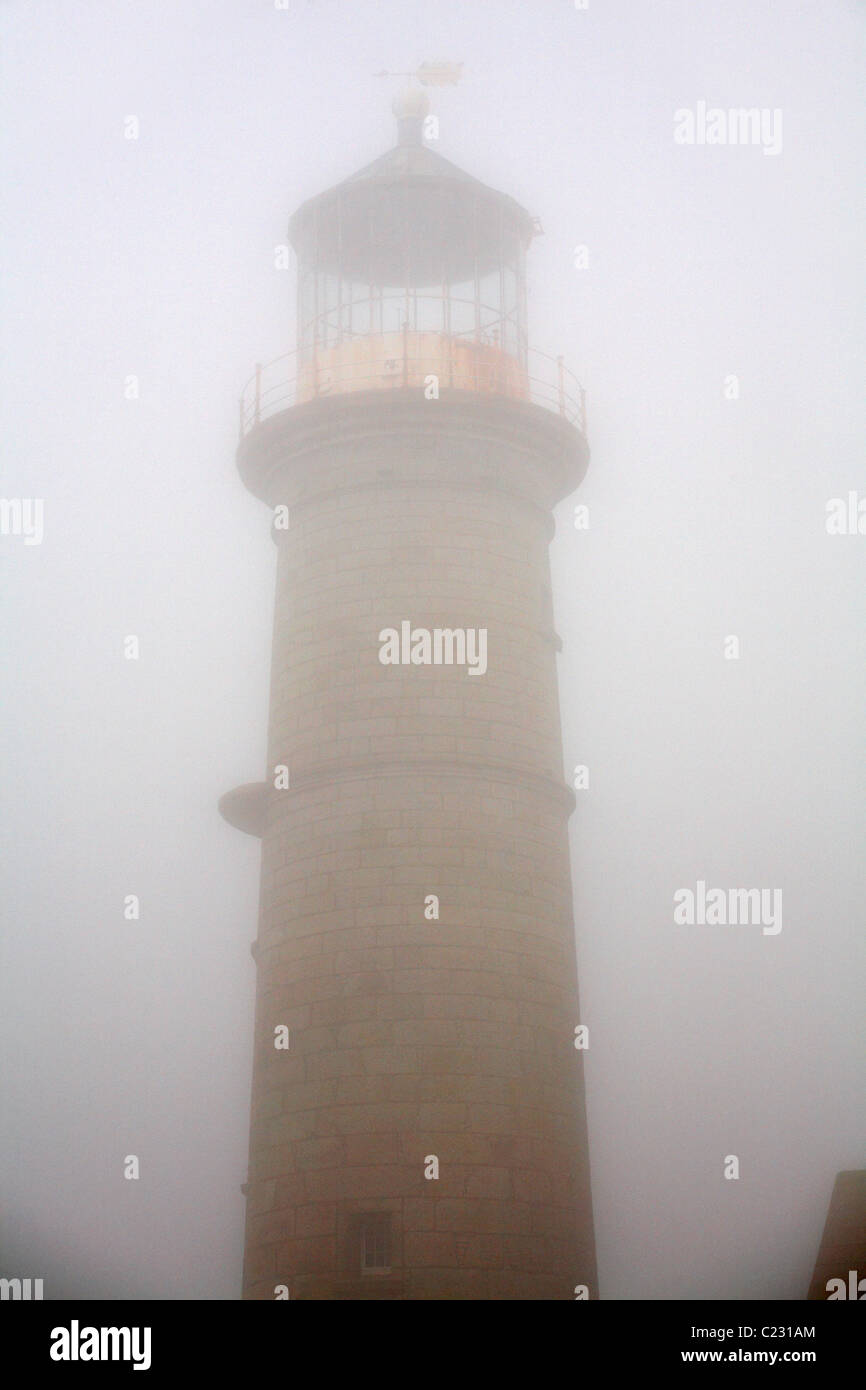 Old Light House lighthouse enveloped by thick fog on Lundy Island, Devon, England UK in March - Stock Image