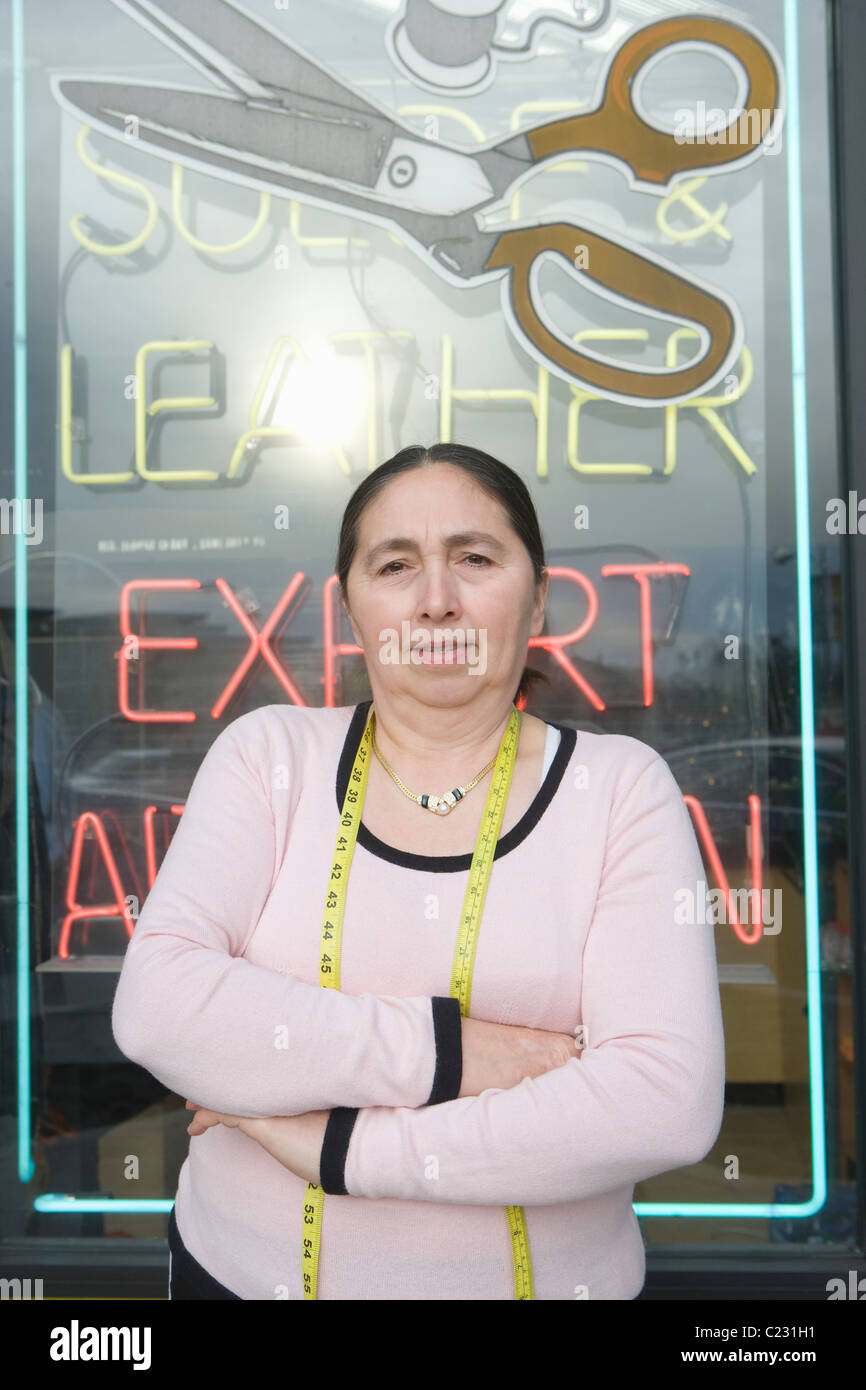 Woman standing infront of laundrette shop window Stock Photo