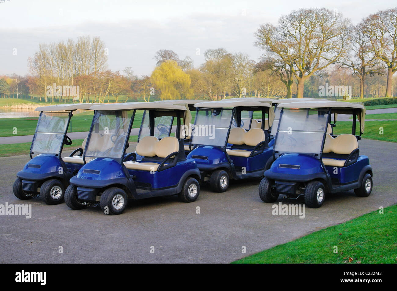 Photo of golf buggies parked up in the morning outside the club house. - Stock Image
