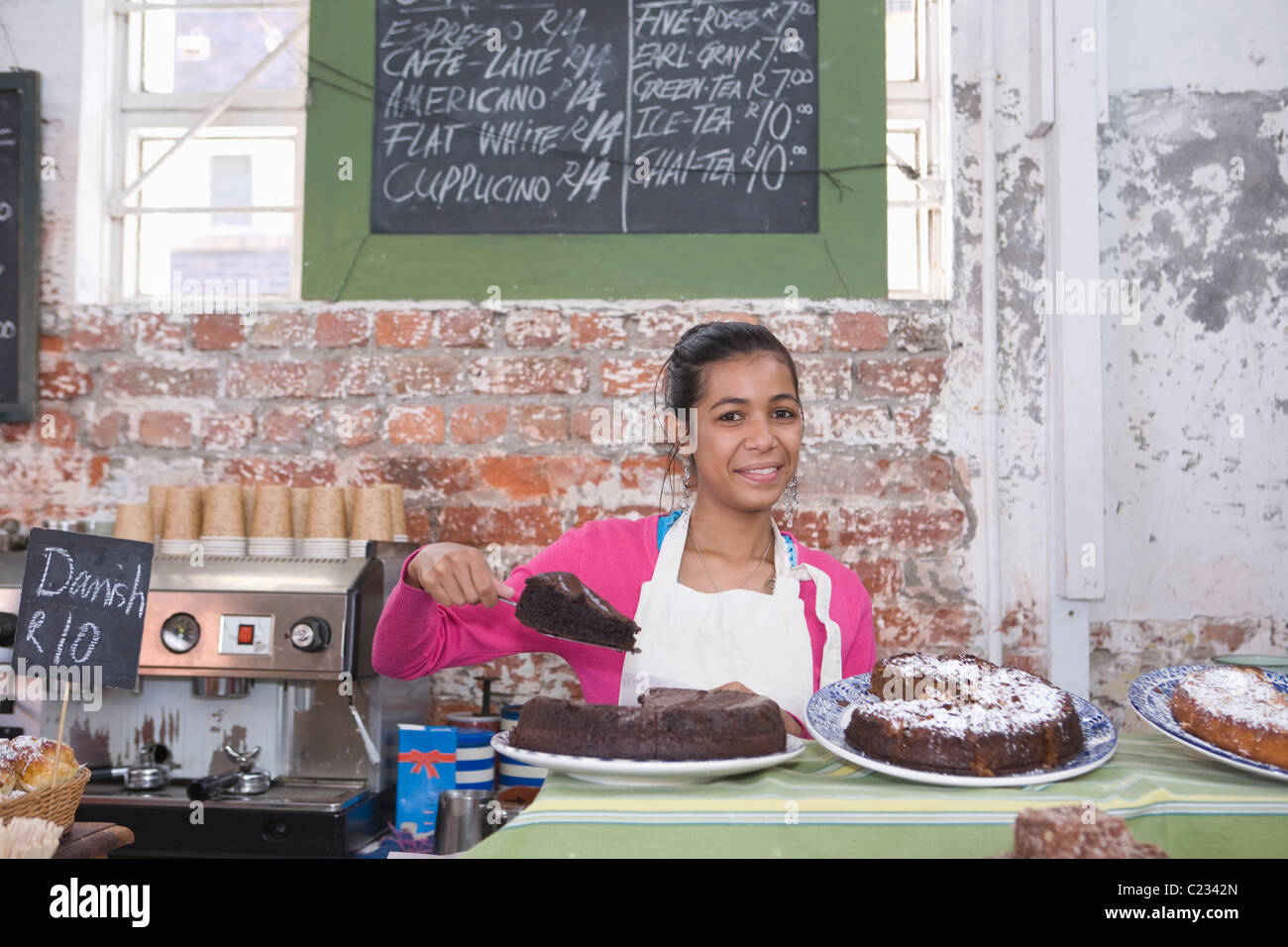 Catering assistant in service area of canteen - Stock Image