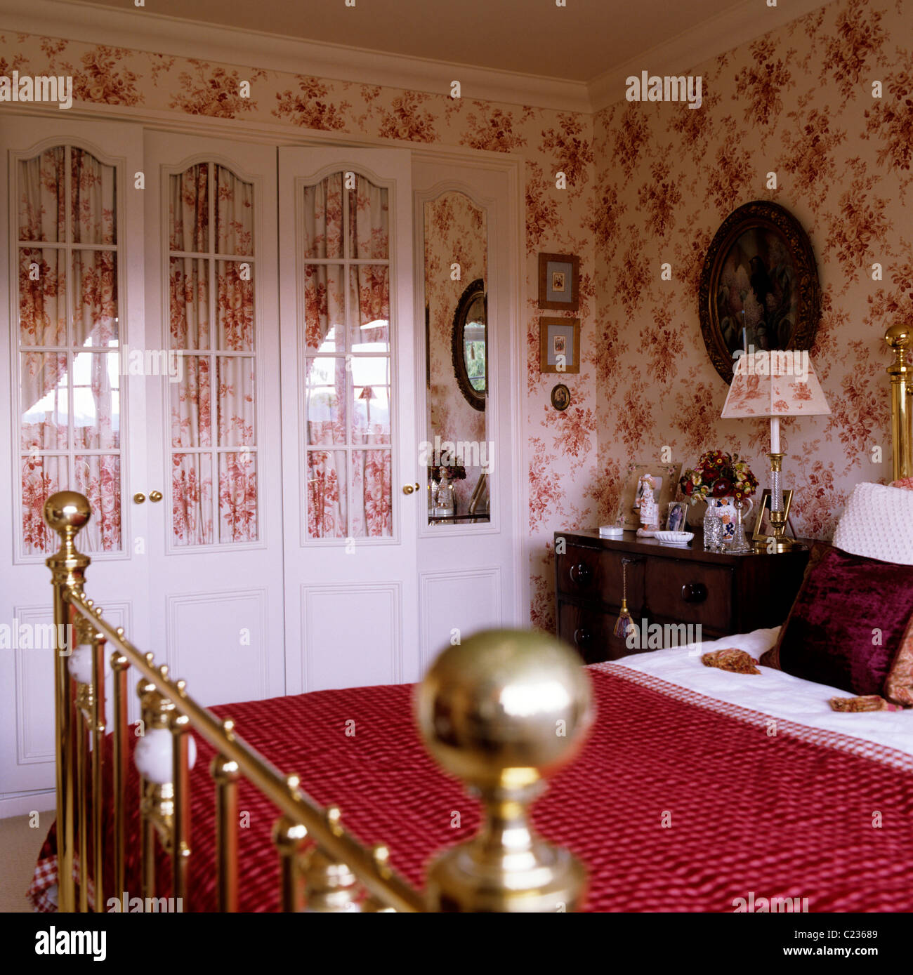 Red Quilt On Brass Framed Bed In Bedroom With Toile De Jouy Wallpaper    Stock Image