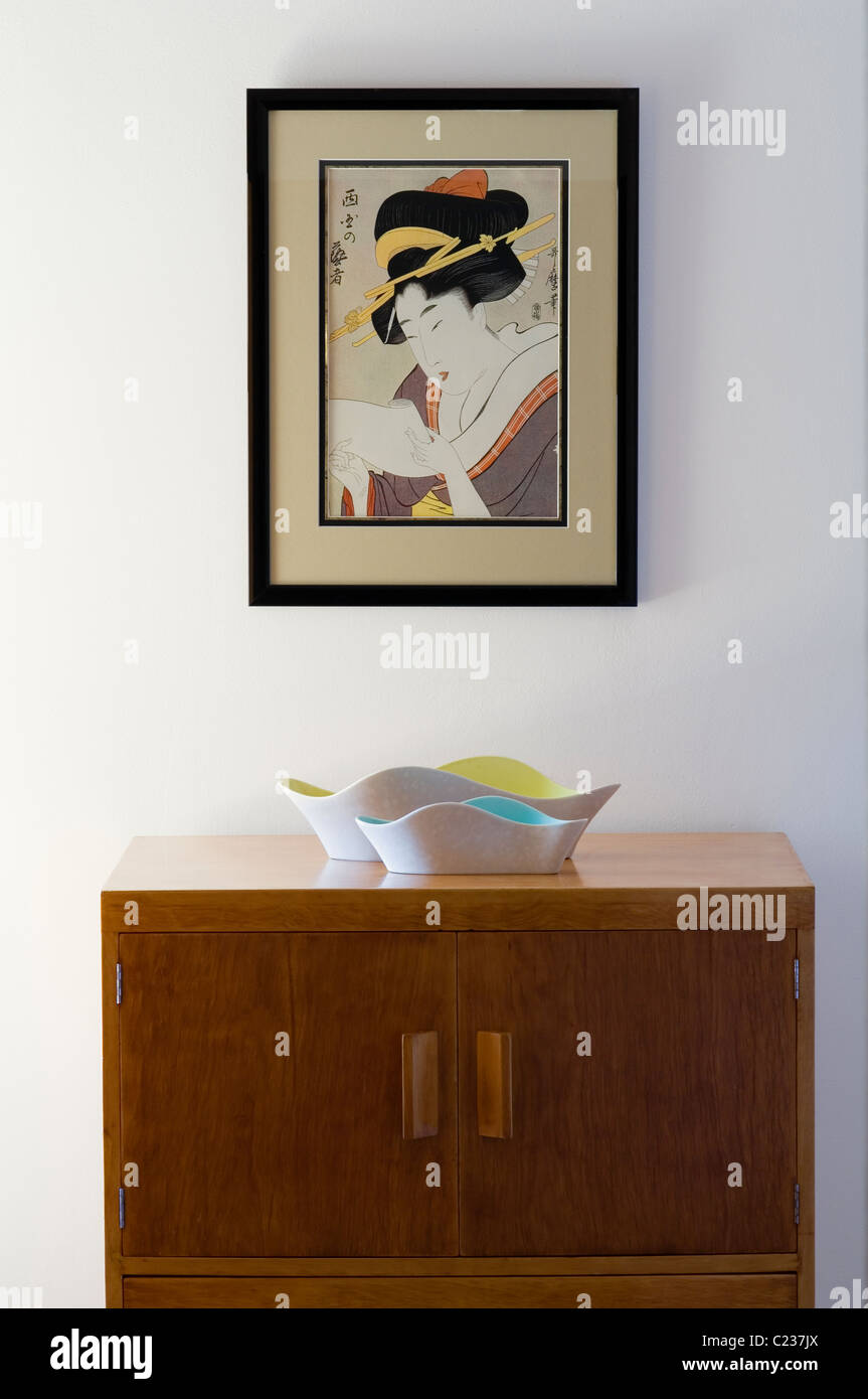 Japanese artwork on white wall above Poole pottery on a Gerald Summers wooden sideboard - Stock Image