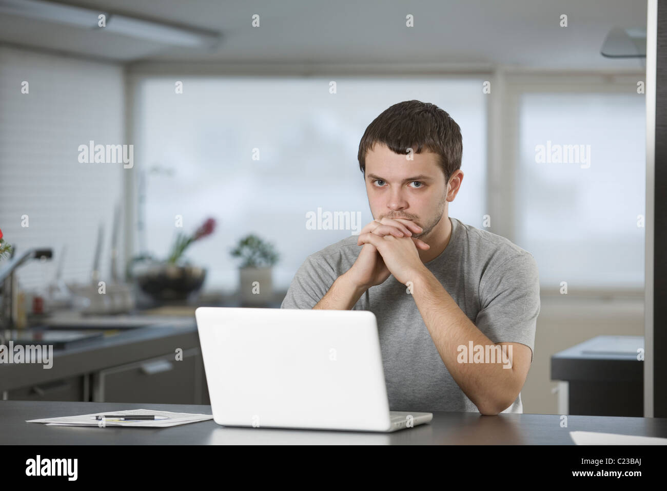 Young man sits leaning on elbows at laptop in kitchen - Stock Image