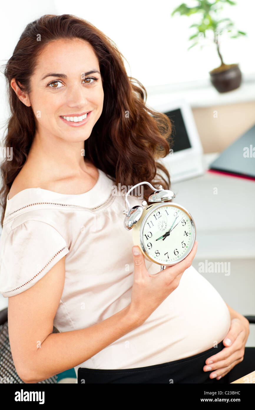 Radiant pregnant businesswoman holding an alarm clock and sitting at her desk - Stock Image