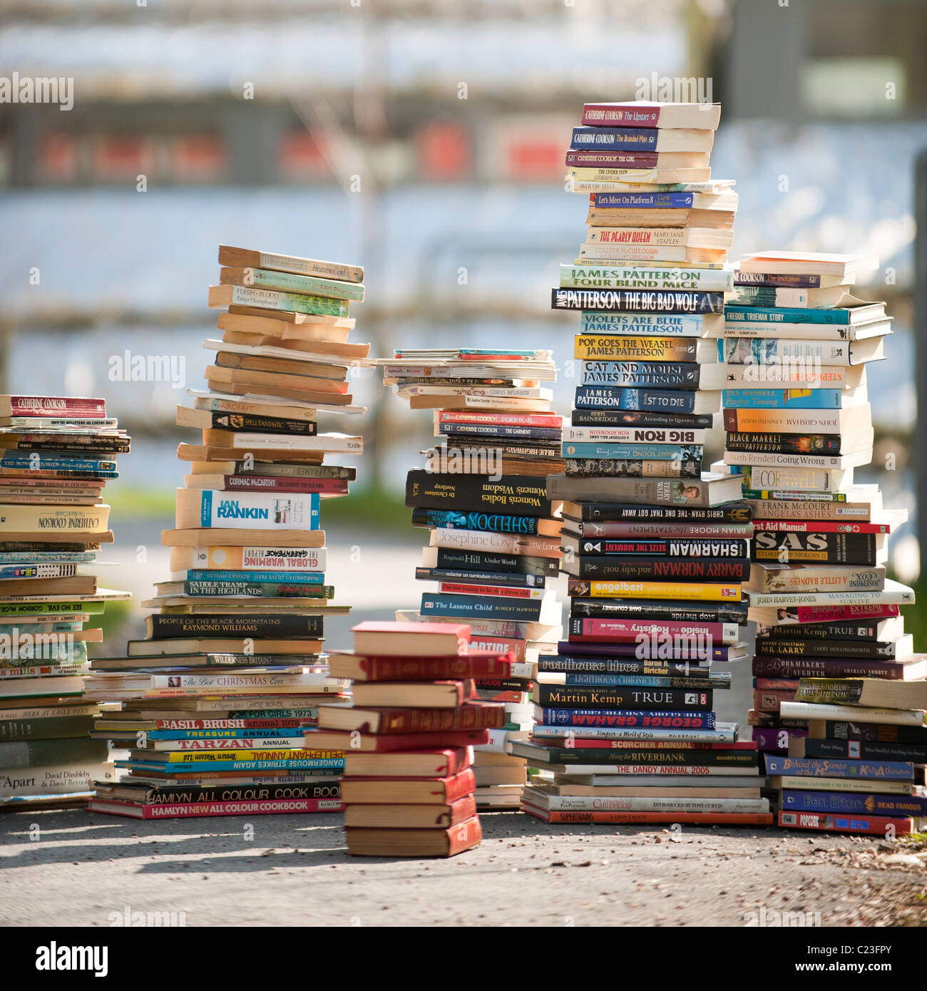stacks of second hand paperback books - Stock Image