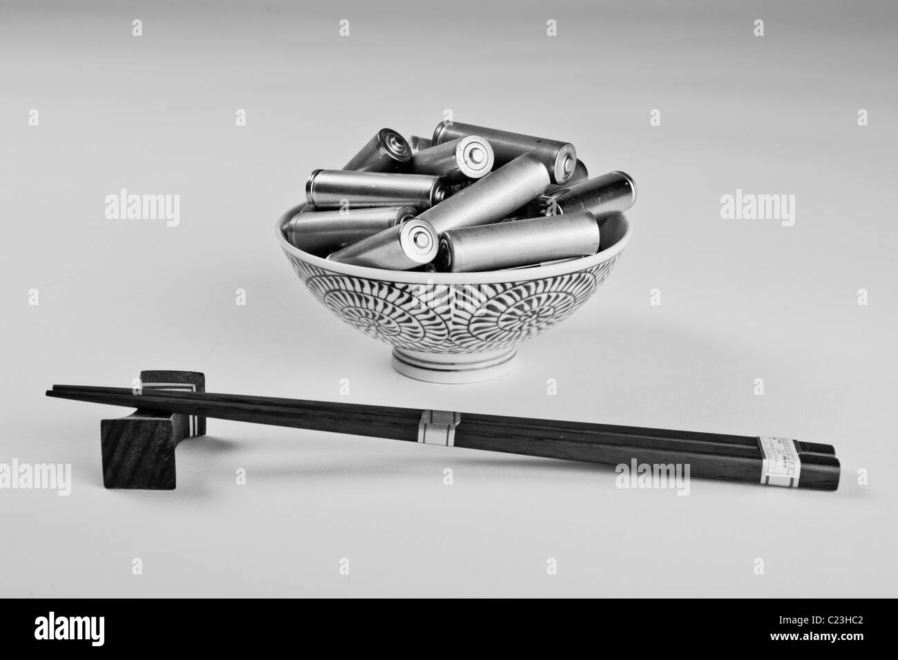 A bowl containing batteries and chopsticks. The photo is a metaphor for consumerism. - Stock Image