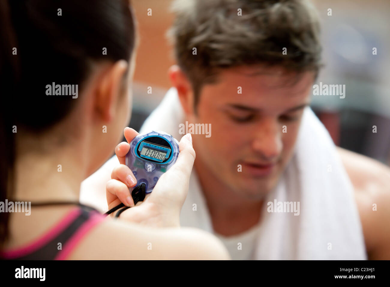 Female trainer holding a chronometer while man doing physical exercise - Stock Image