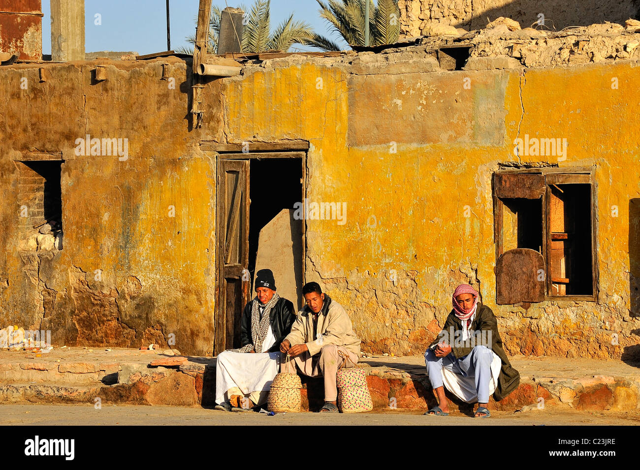 Three Egyptian men sitting on a sidewalk in front a house in a street of the city of Siwa, western desert, Egypt - Stock Image