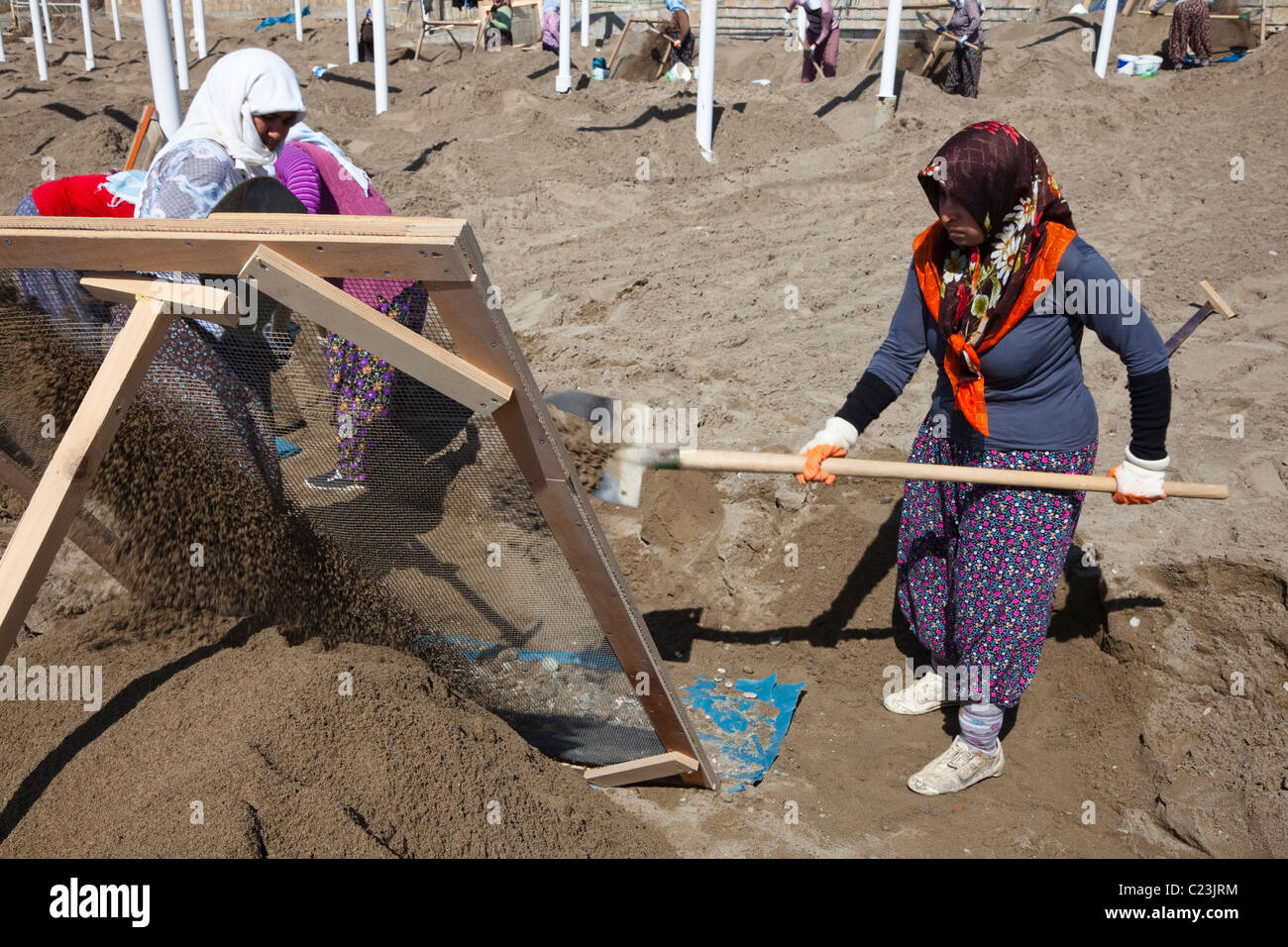 Turkish women working on the beach at Belek,Turkey, cleaning the sand of all stones, by sifting the sand through - Stock Image