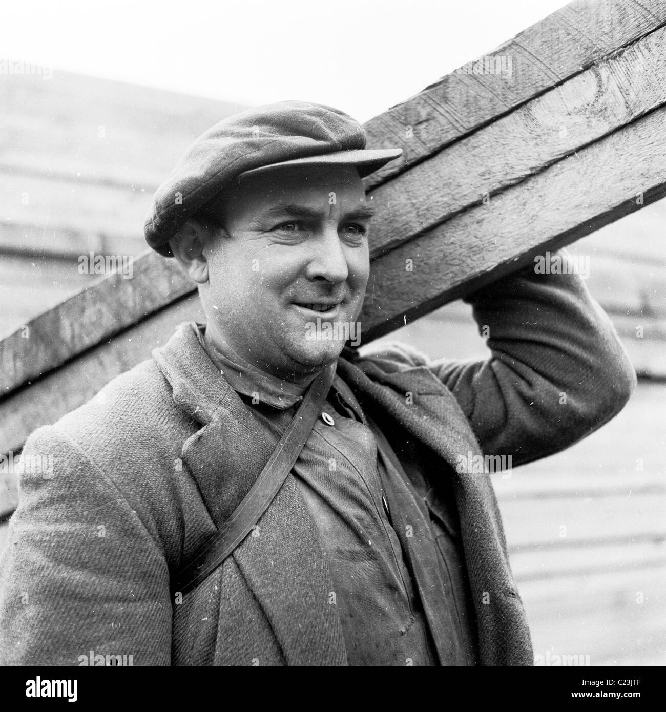 1950s, England. Building worker wearing flat cap and jacket carries planks of wood in this historical picture by - Stock Image