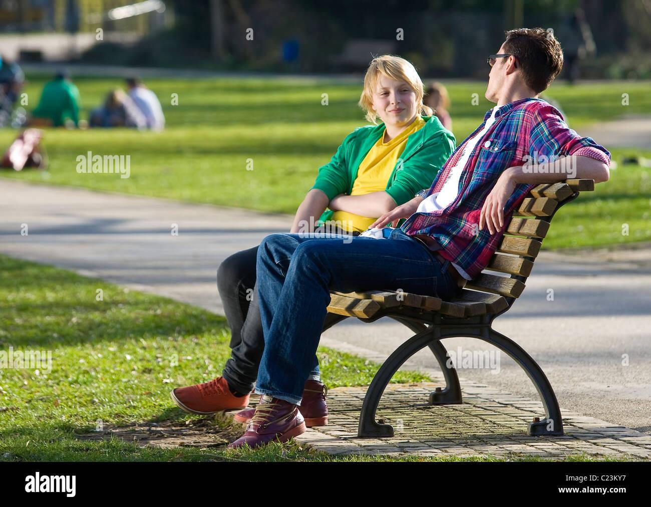 Ein junger Mann und ein Junge unterhalten sich auf einer Parkbank sitzend an einem Frühlingstag im Sonnenschein. - Stock Image