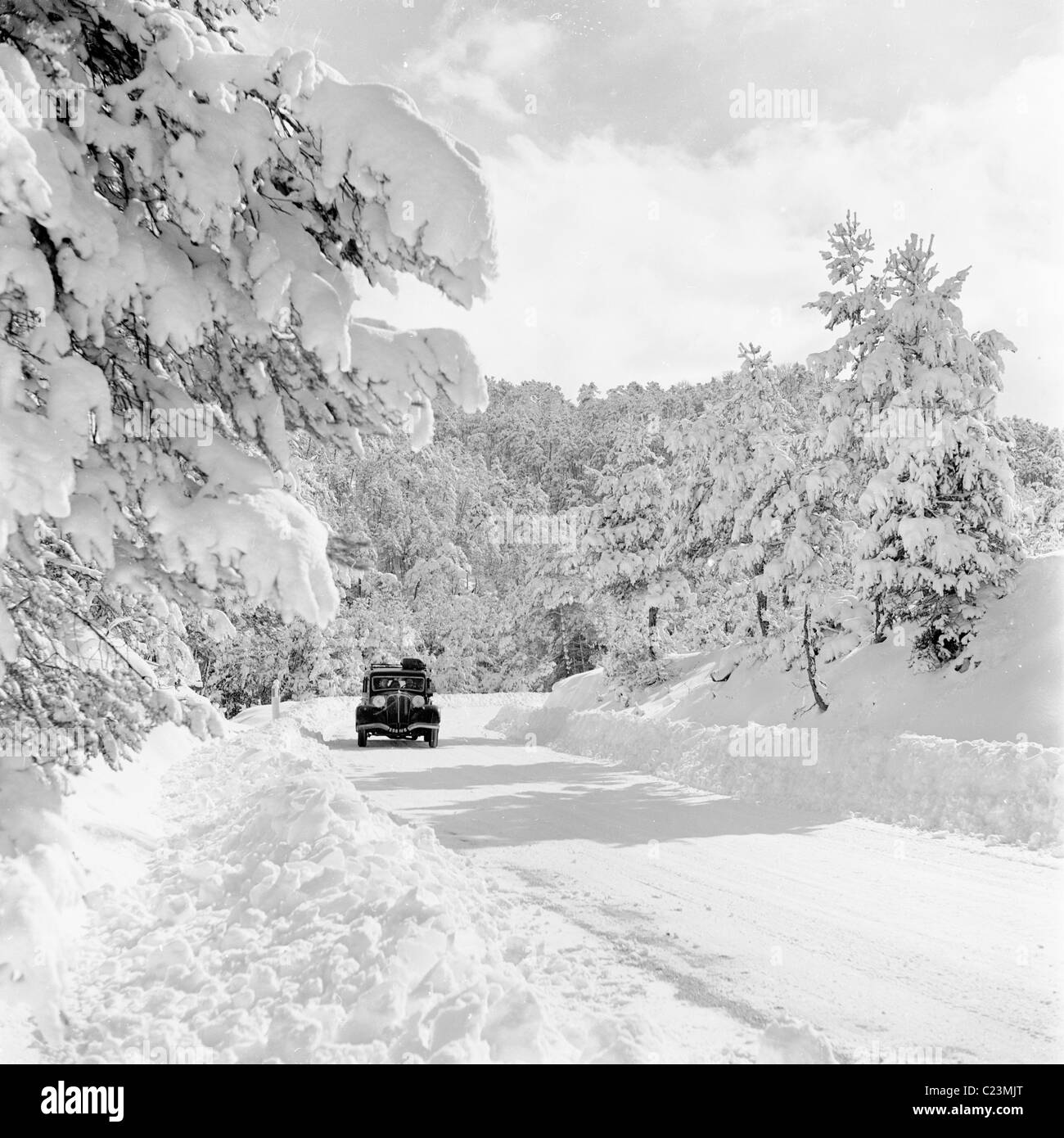 1950, France.  Car travels on a snow covered road in Provence in this historical photograph by J Allan Cash. - Stock Image
