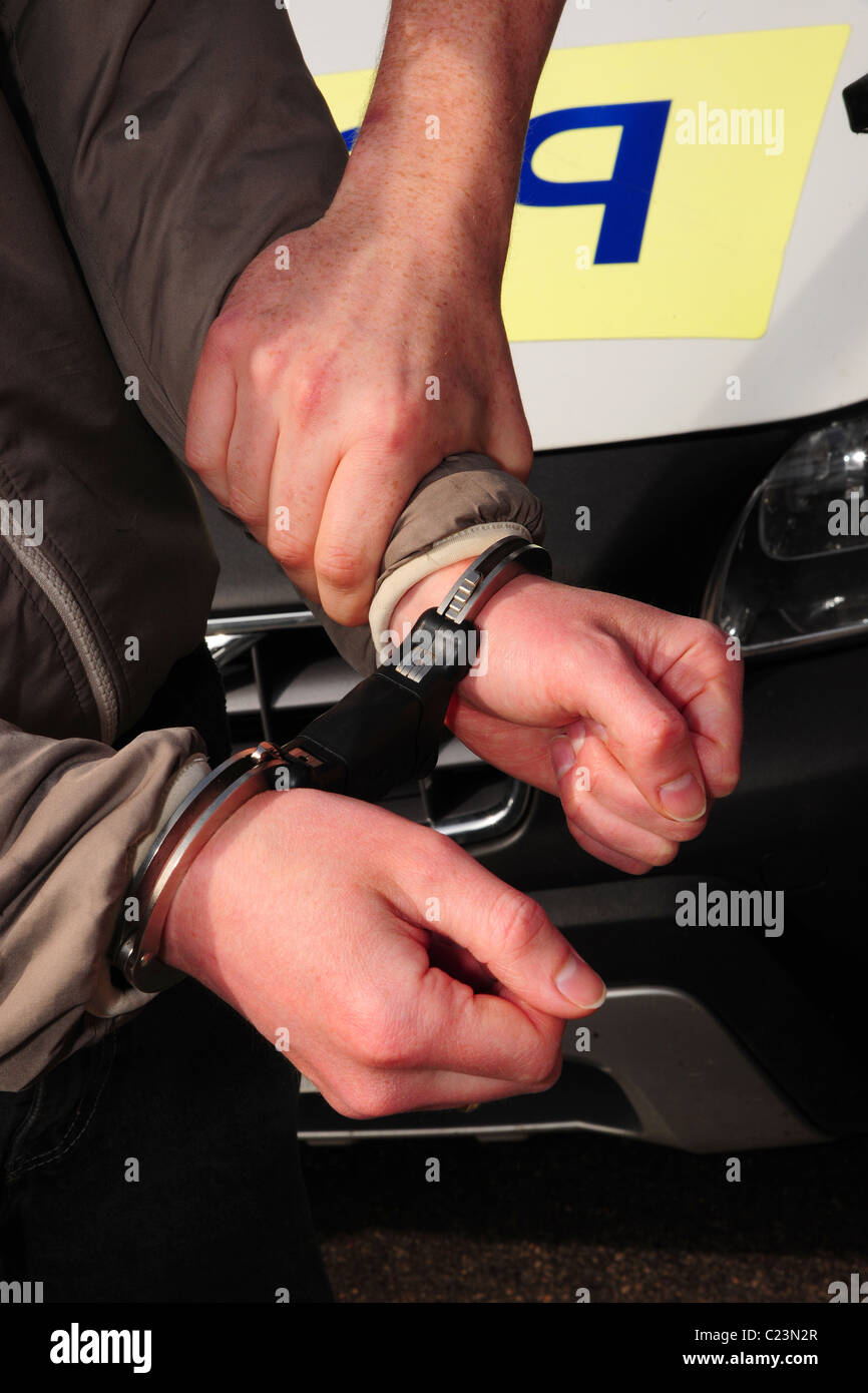 detail of a suspect being handcuffed and detained by a police officer. - Stock Image