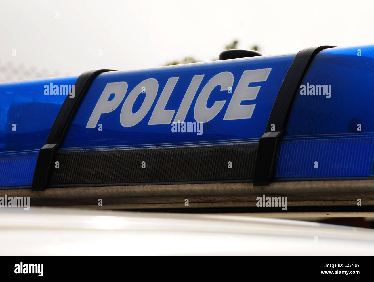 Police vehicle light array showing police in white on blue light. - Stock Image