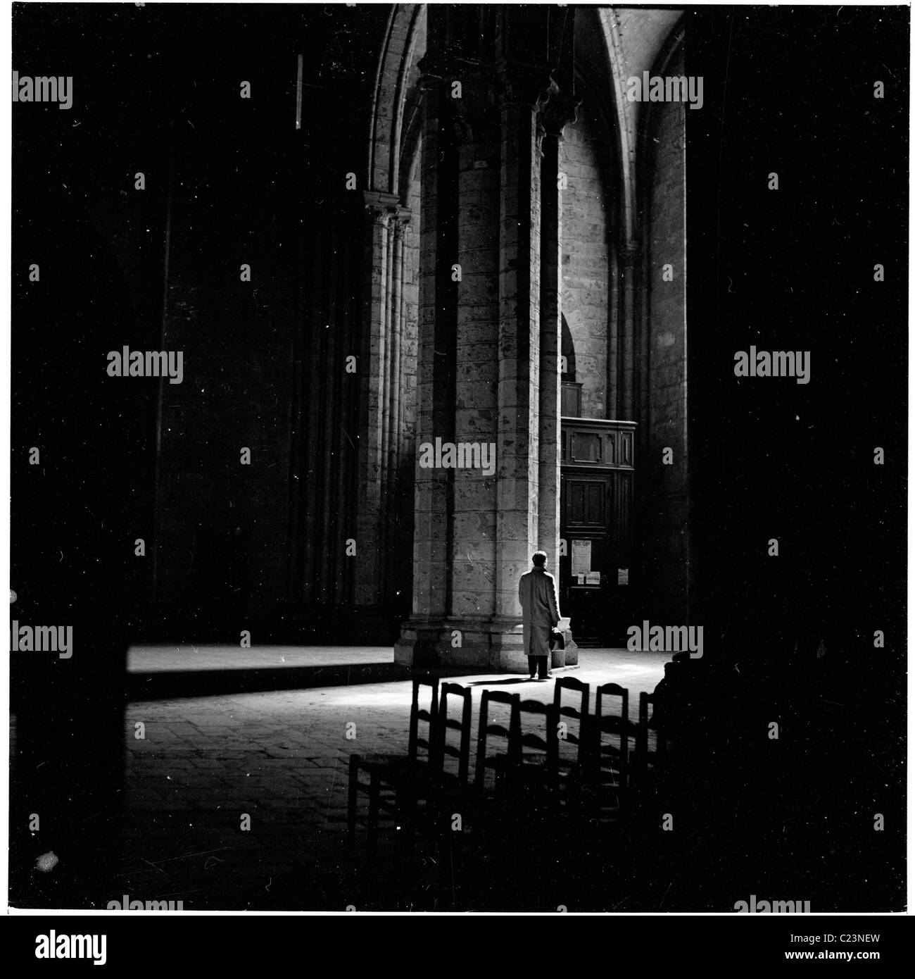 France, 1950s. Visitor stands by a large column inside the Cathedral of Chartres in this historical photograph by - Stock Image