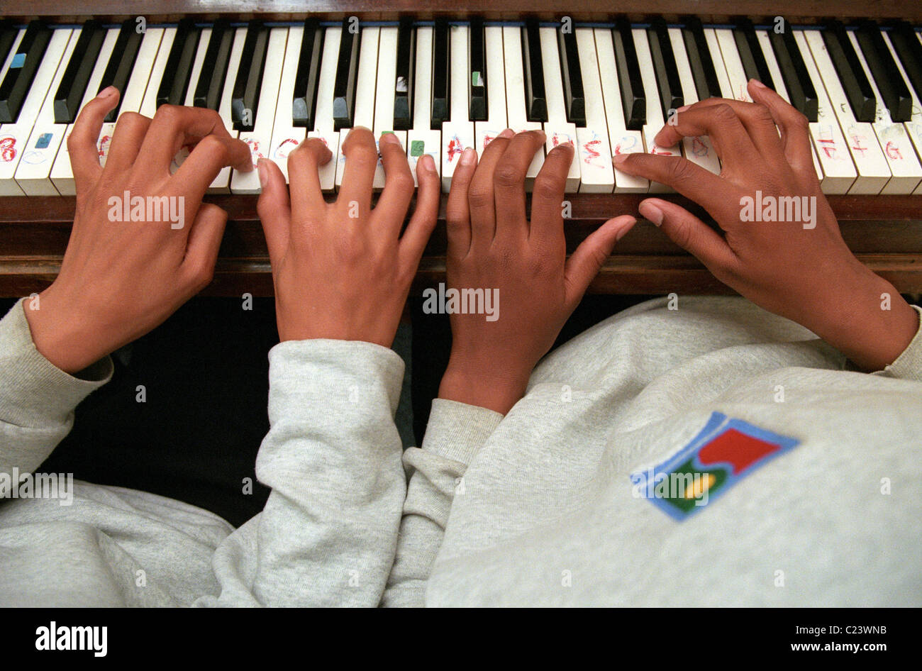 Two Pupils playing duets on the piano at school music lesson - Stock Image