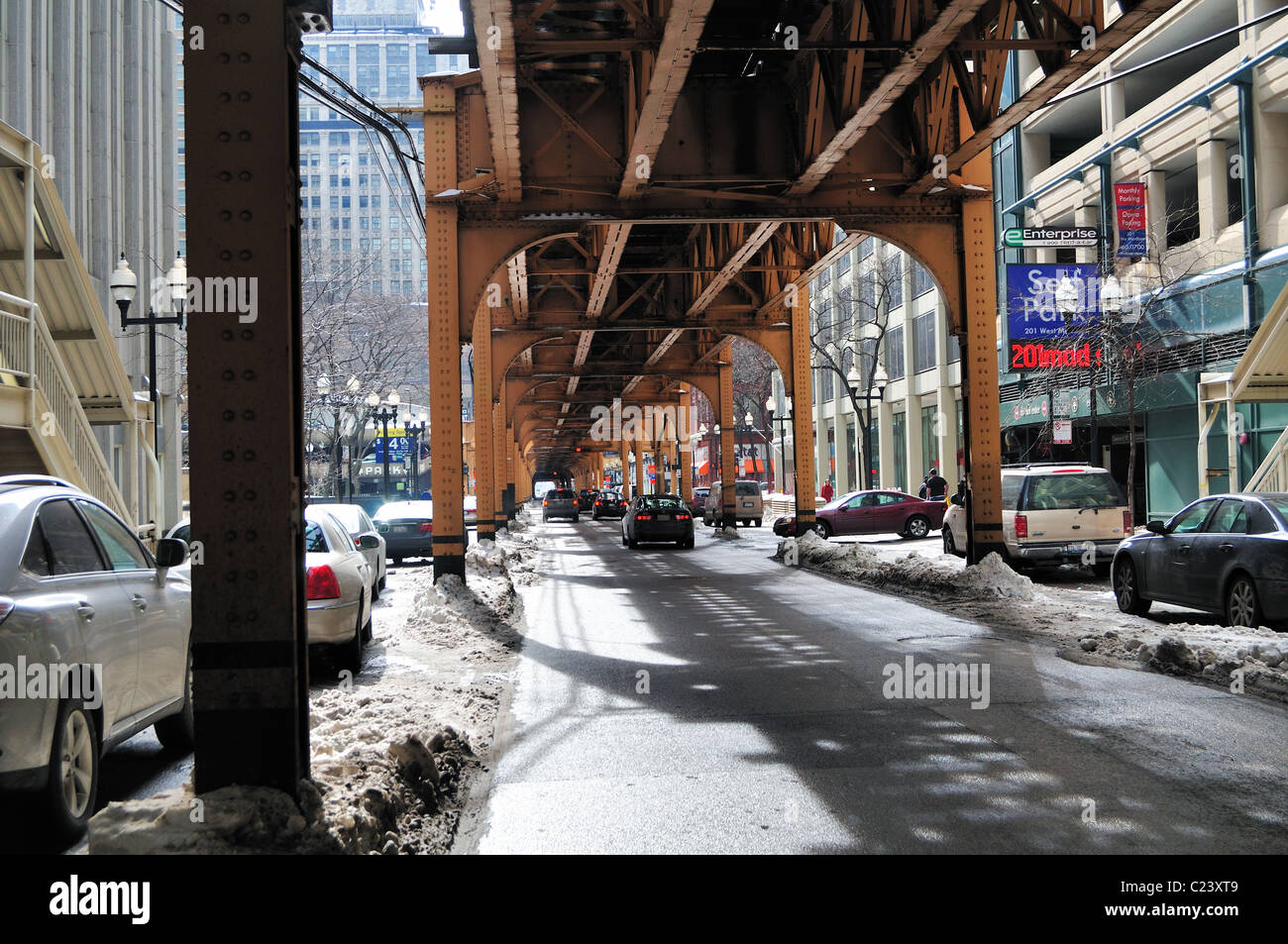 Winter in the city following a storm as snow and slush piles up around the girders supporting elevated train tracks - Stock Image
