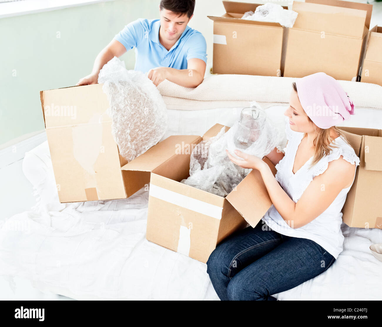 Happy young couple unpacking boxes with glasses - Stock Image