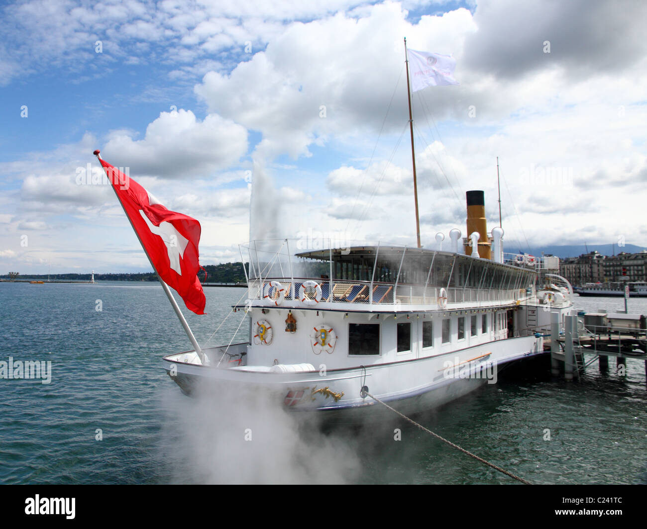 famous paddle steamboat on lake Geneva anchored in front of city Geneva releasing steam with swiss flag - Stock Image