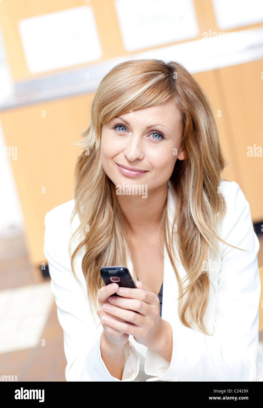 Radiant businesswoman sending a text message with her cellphone - Stock Image