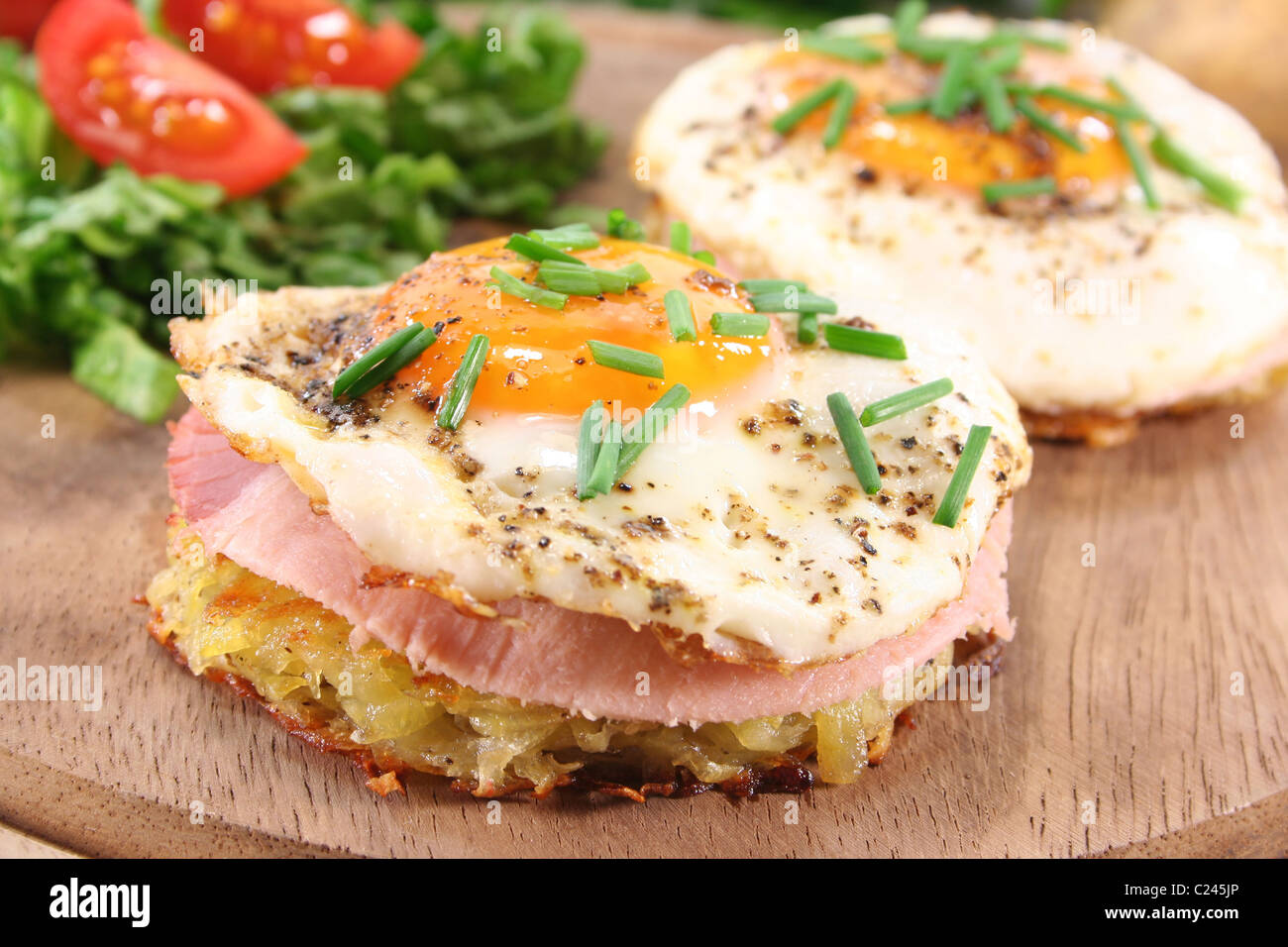 Potato pancakes with ham, egg, pepper, chives and fresh salad - Stock Image