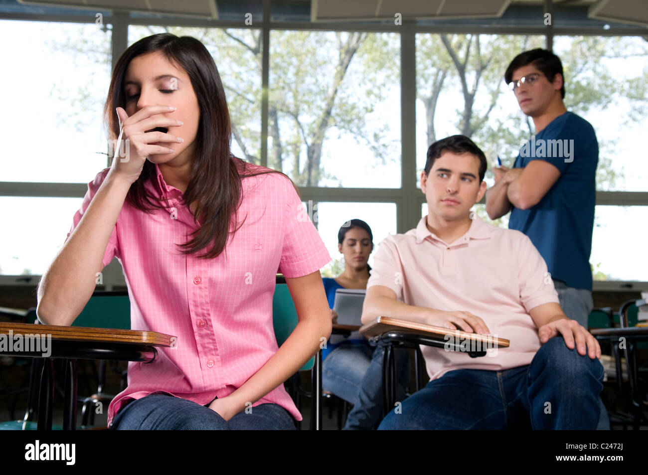 Female student yawning in class - Stock Image