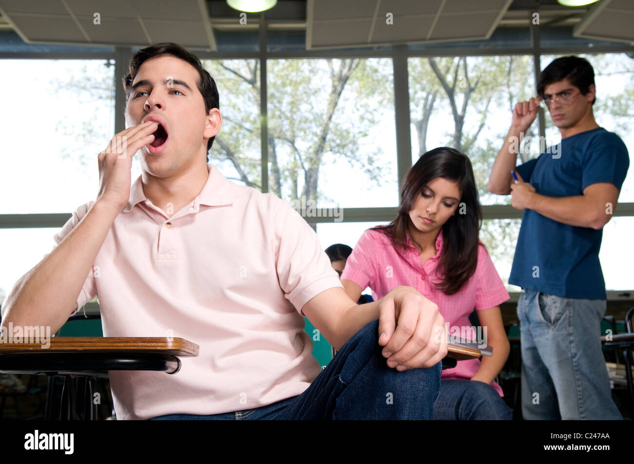 Male student yawning in class - Stock Image
