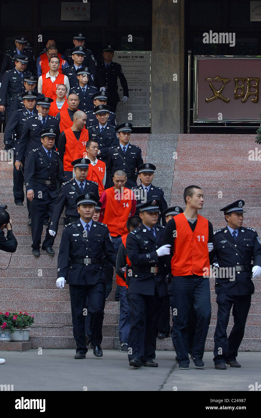 Accomplices of Xie Caiping are escorted to leave the court after the sentences  She is known as the 'Godmother - Stock Image