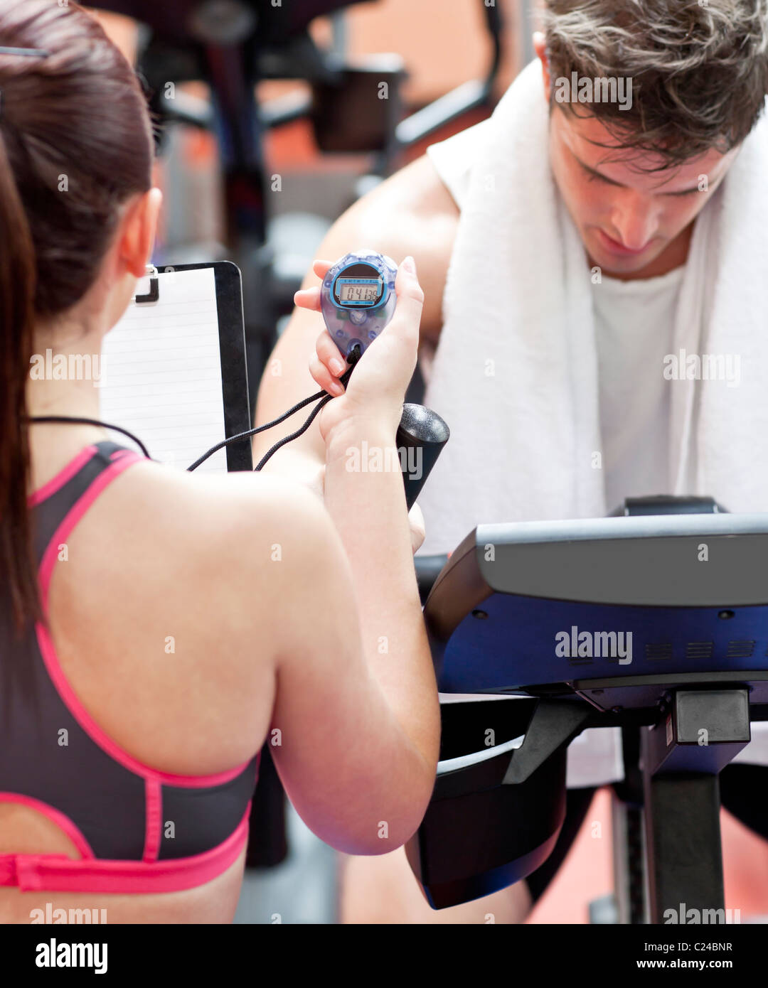 Close-up of a coach using a chronometer while man is doing physical exercises - Stock Image