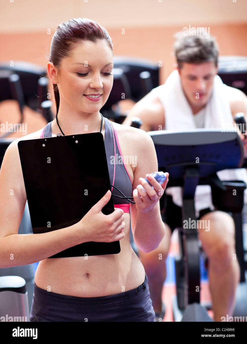 Joyful coach holding a chronometer with man in the background doing physical exercises - Stock Image