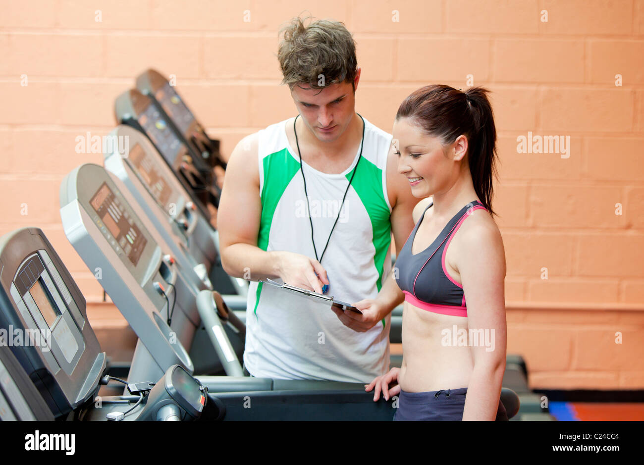 Serious coach giving instruction to a female athlete standing on a treadmill - Stock Image