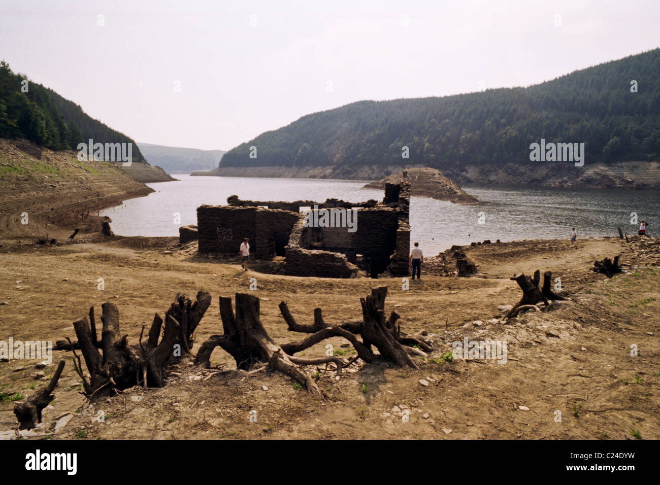 Visitors looking at Fannog farmhouse in Llyn Brianne Reservoir exposed in the summer drought of 1995 Mid Wales UK - Stock Image