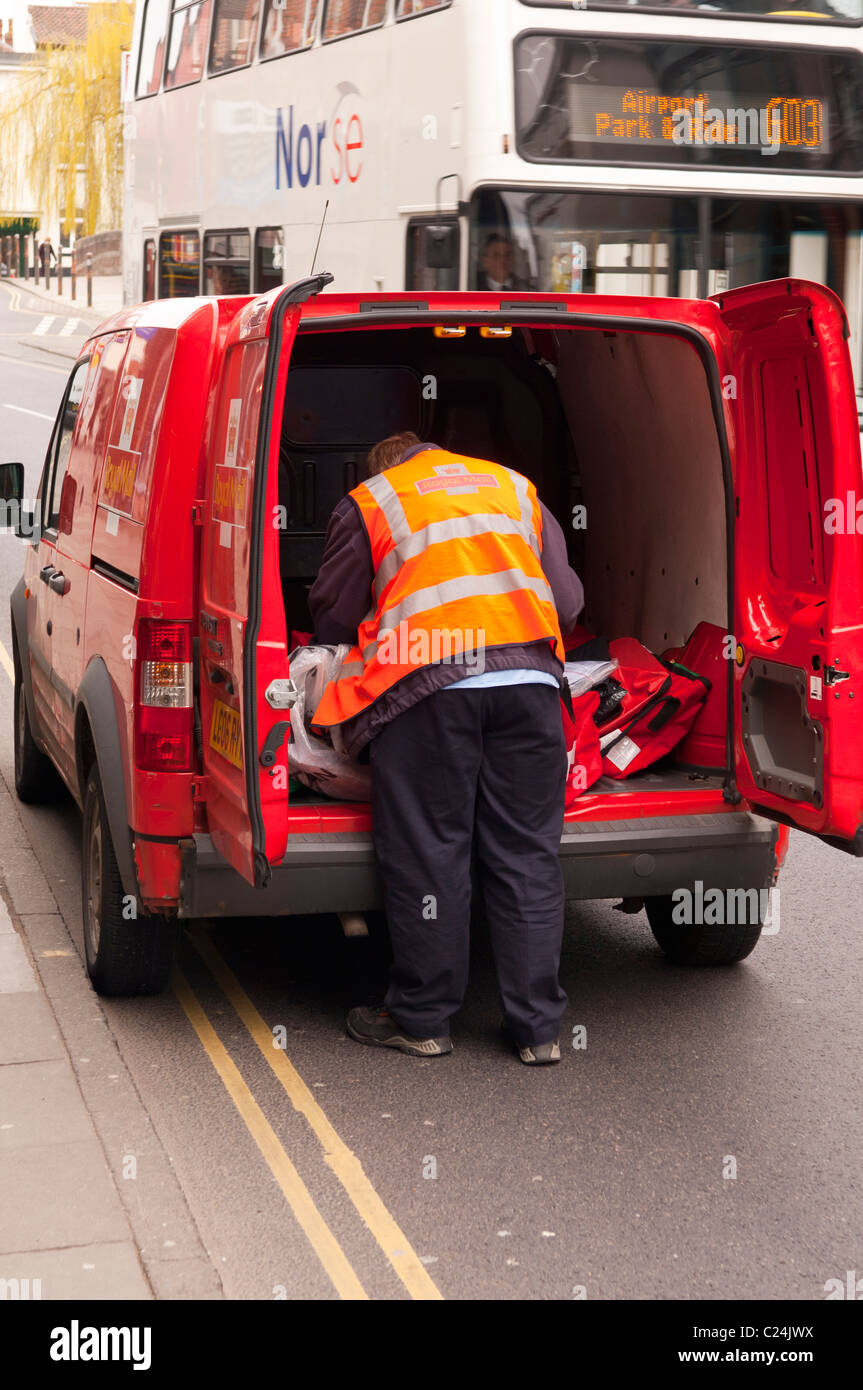 A Royal Mail postman getting mail from his van in Norwich , Norfolk , England , Britain , Uk - Stock Image
