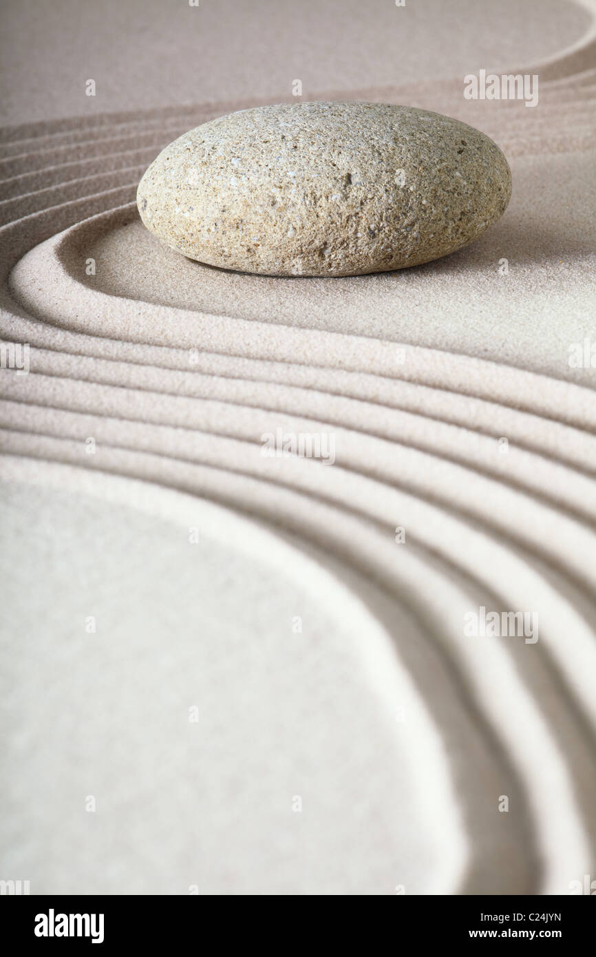 zen garden japanese garden zen stone with raked sand and round stone tranquility and balance ripples sand pattern - Stock Image