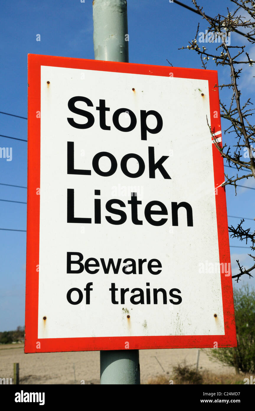 Stop Look Listen Beware of Trains Warning Sign at a Level Crossing, Harston, Cambridgeshire, England, UK - Stock Image