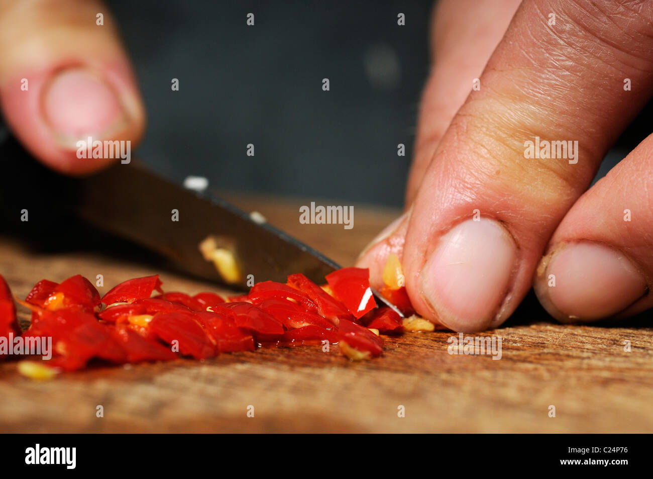 Stock photo of a woman chopping chillis on a wooden table. - Stock Image