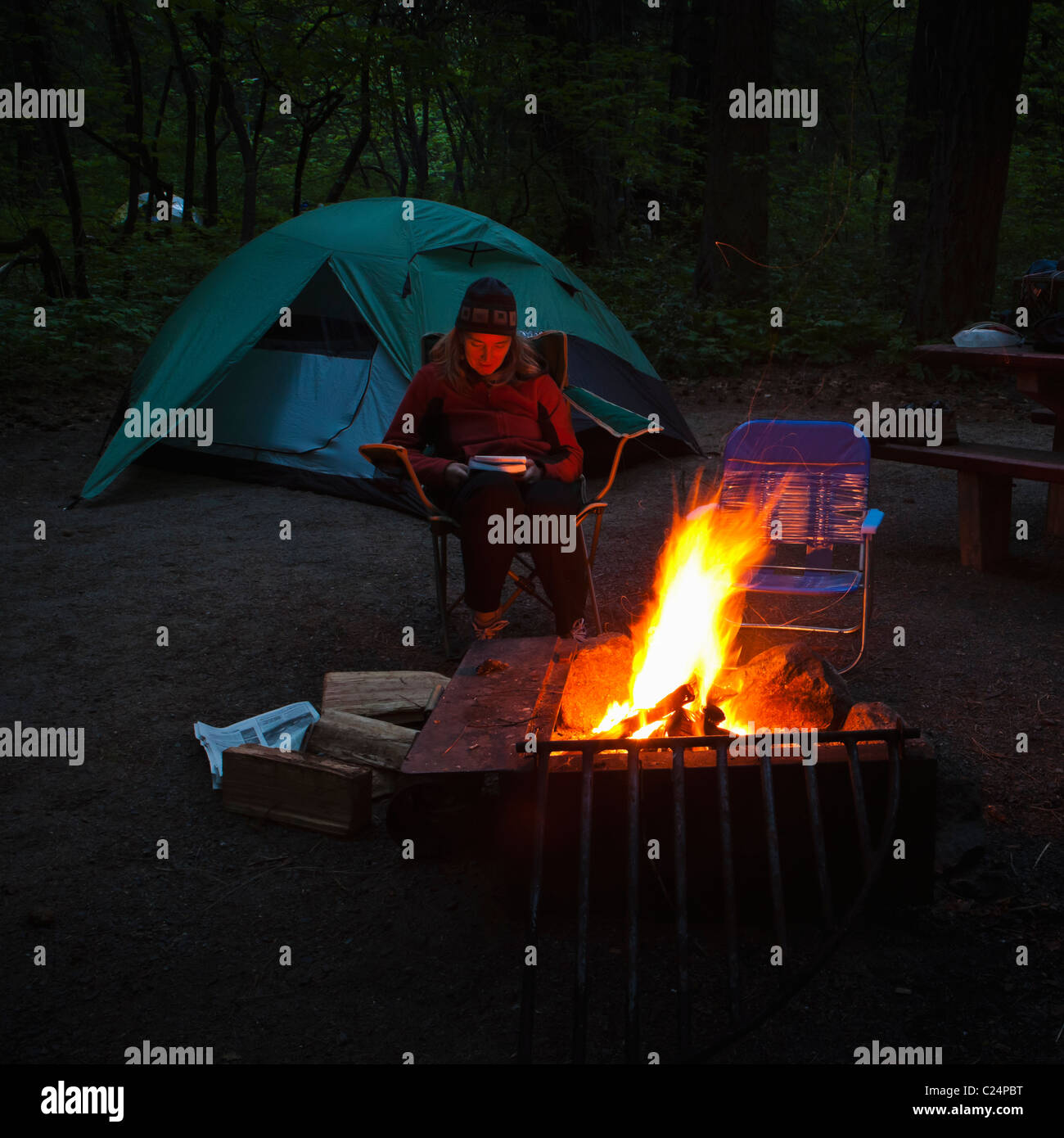 A middle aged woman sitting reading a book next to a camp fire. - Stock Image