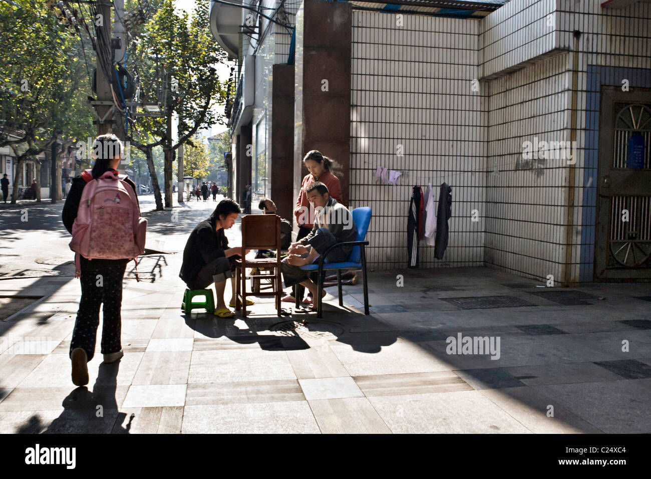 CHINA, WUHAN: Street scene in Wuhan with men playing a card game on chairs on the sidewalk, a young girl with a - Stock Image