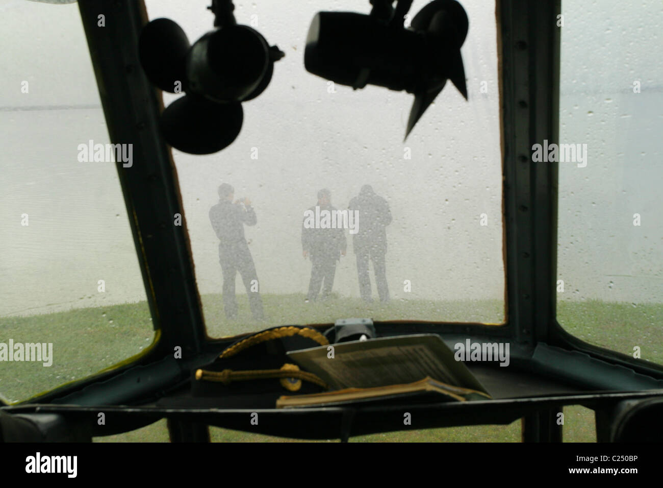 From the helicopter cabin you can see three figures of helicopterists in the overcast. Yamal peninsula, RUSSIA - Stock Image