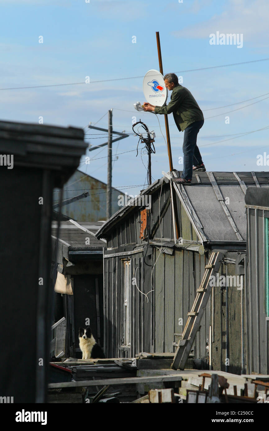Man assemble dish satellite TV on his roof. Settlement Mys-Kamenny, Yamal peninsula, RUSSIA - Stock Image