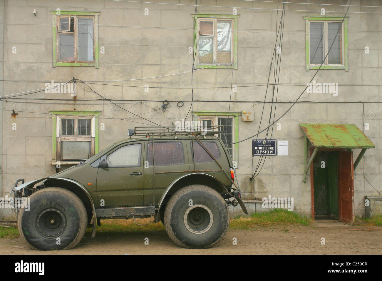 Car on the low pressure wheels parked near postal telegraph office. Settlement Mys-Kamenny, Yamal peninsula, RUSSIA - Stock Image