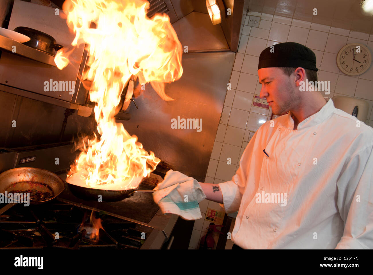 Chef cooking in a kitchen with flames coming out of the frying pan restaurant