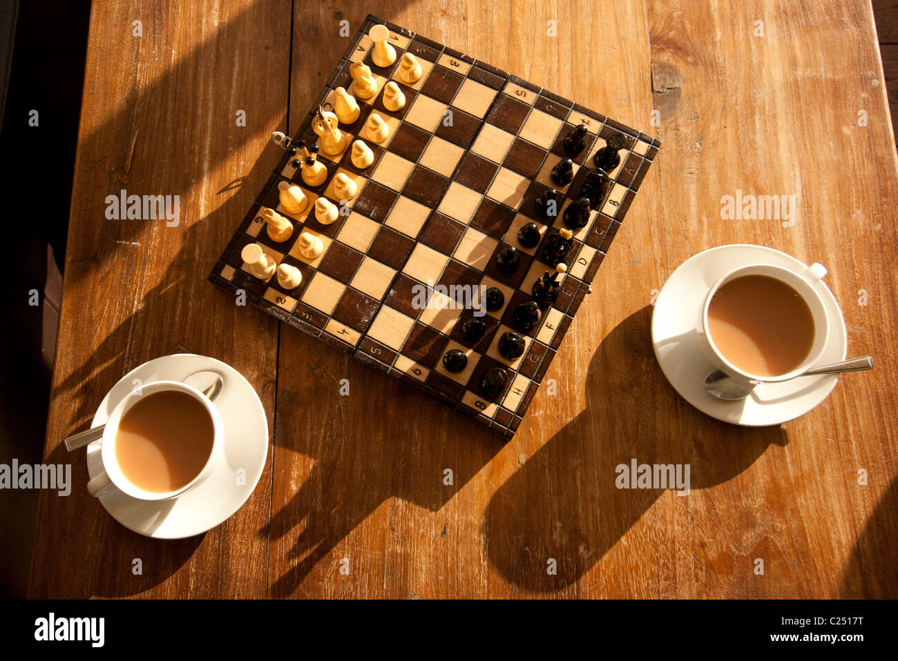 Game Of Chess Set Out On A Coffee Table With Two Cups Of Tea.